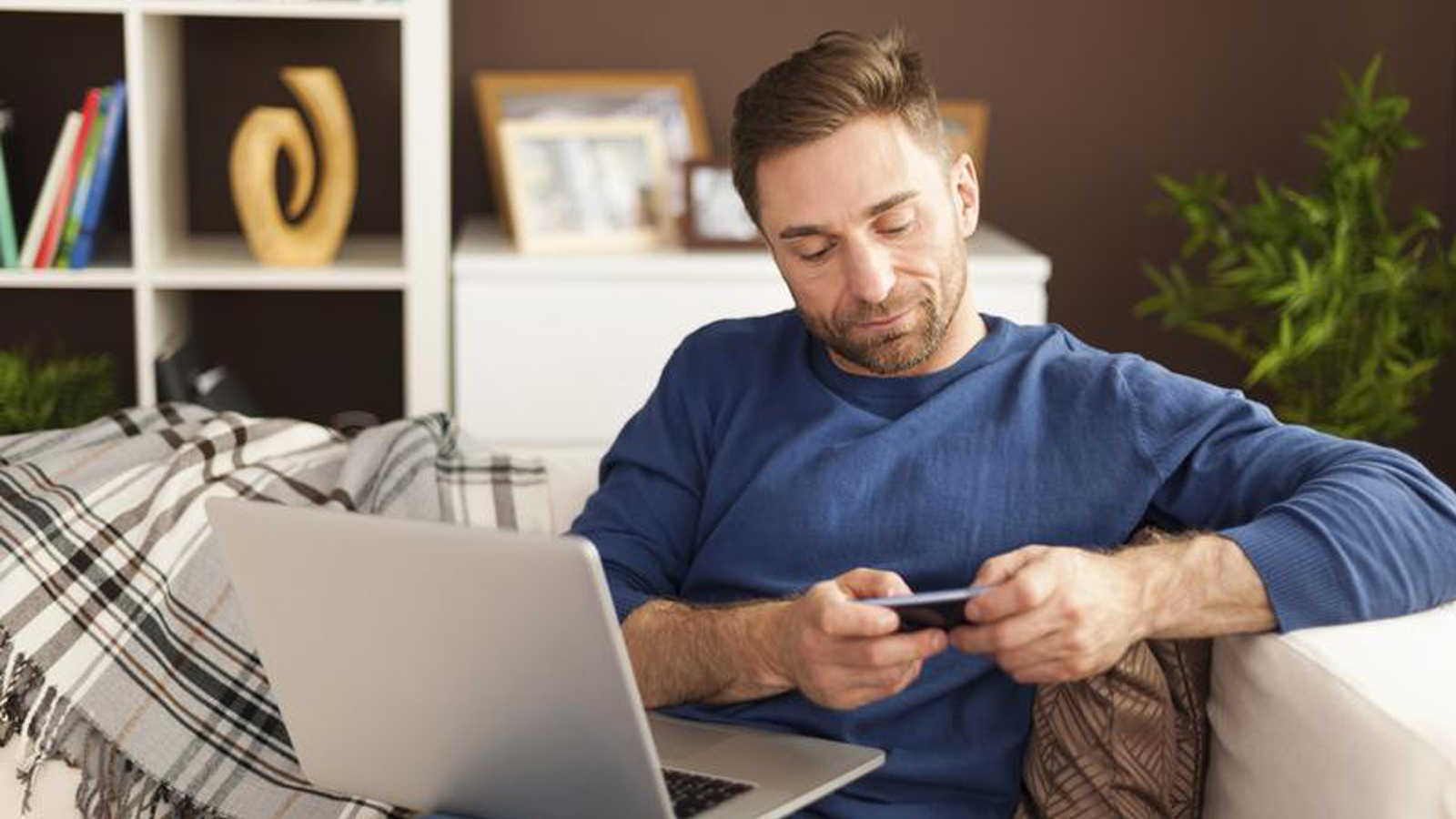 Man on a couch with a laptop using a mobile phone