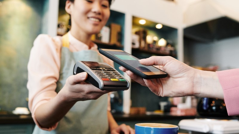 Young female Asian barista holding payment terminal while customer paying for cappuccino with modern smartphone, close-up view